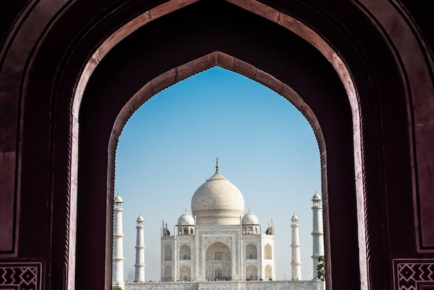 Taj mahal, ivory-white marble, front centre view with blue sky in agra, india.