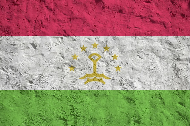 Tajikistan flag depicted in bright paint colors on old relief plastering wall. textured banner on rough background