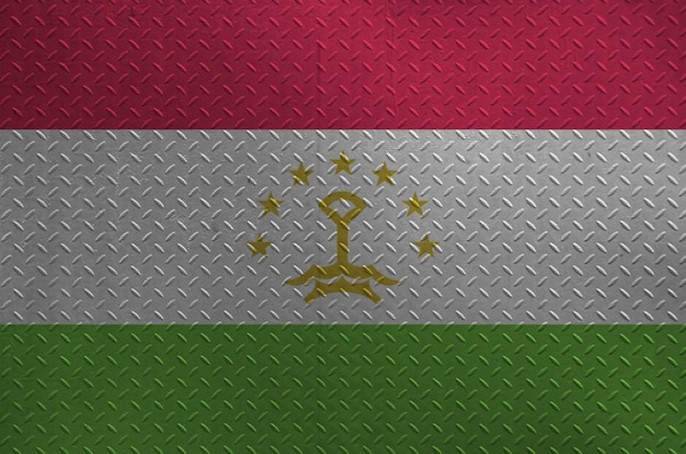 Tajikistan flag depicted in paint colors on old brushed metal plate or wall closeup. textured banner on rough background