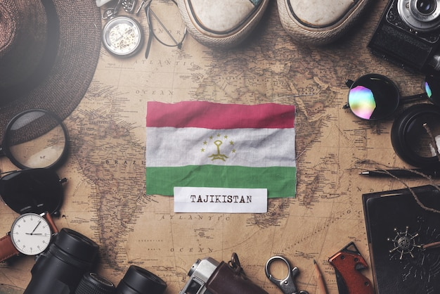 Tajikistan flag between traveler's accessories on old vintage map. overhead shot