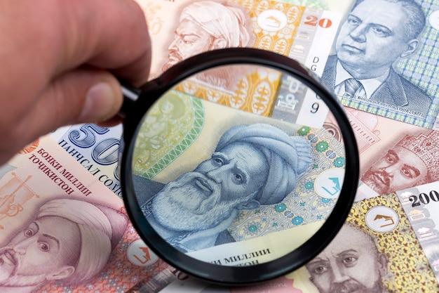 Tajikistani somoni in a magnifying glass a business background