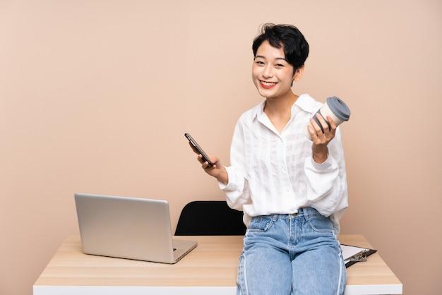 Takにコーヒーを保持している彼女の職場で若いビジネスアジア女性