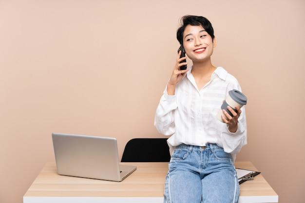 Takにコーヒーを保持している彼女の職場で若いビジネスアジアの女性