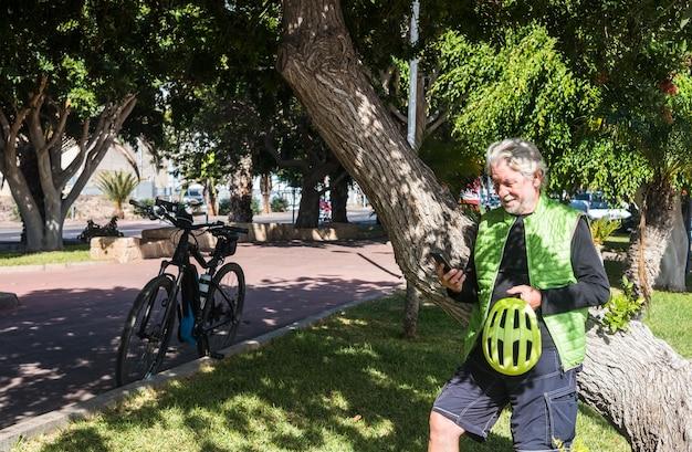 電動自転車で休憩してください。携帯電話をチェックしながら大きな木の幹に寄りかかって70歳の老人とスポーティな男性の正面図。健康的な生活様式