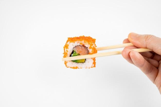 Возьмите калифорнийские маки-роллы с бамбуковыми палочками и залейте соевым соусом. розовый имбирь, васаби. азиатская еда, японская кухня фон