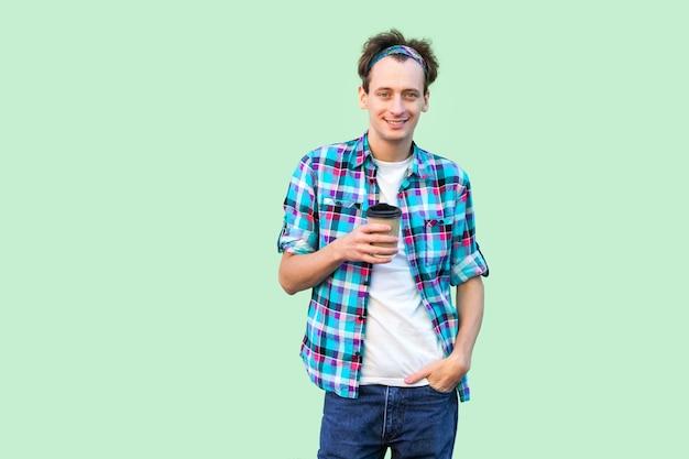 コーヒーブレイクを取ります。白いtシャツと市松模様のシャツを着た若い流行に敏感な男がポケットに手を入れて朝のコーヒーと紙コップを持って立っています。屋内、孤立した、スタジオショット、緑の背景