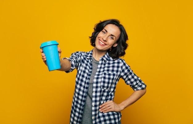 내 새 열 머그를보세요! 카메라에 미소를 짓고있는 젊은 매력적인 학생의 열 머그잔에 초점을 맞춘 사진은 그녀가 좋아하는 편안한 파란색 열 머그잔을 뻗은 손에 들고 있습니다.