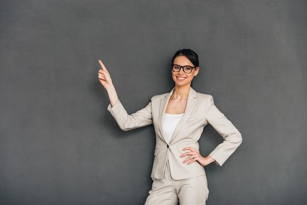 Взгляните сюда! веселая молодая деловая женщина в очках, указывая на пространство для копирования и глядя в камеру с улыбкой, стоя на сером фоне
