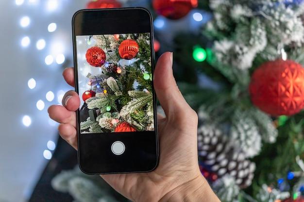 크리스마스 트리의 생생하고 아름다운 사진을 찍으십시오. 블로거는 소셜 미디어를 위해 촬영합니다. 눈 속에서 아름 다운 크리스마스 트리입니다.