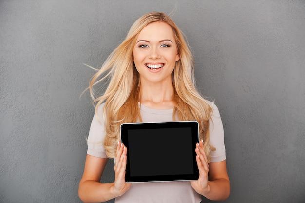 현대 기술을 활용하십시오! 디지털 태블릿을 들고 즐거운 젊은 여성