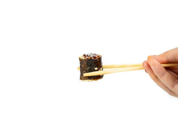 Возьмите роллы унаги маки с бамбуковыми палочками для еды на белом фоне, азиатская еда, японская кухня