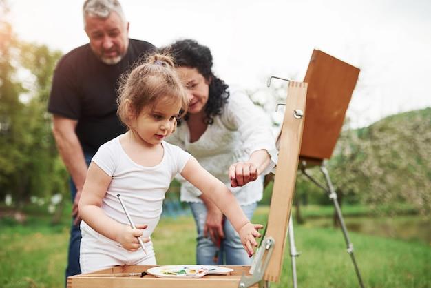 これには別の色を使用してください。祖母と祖父は孫娘と屋外で楽しんでいます。絵画の構想