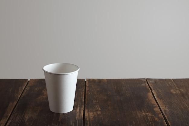 Porta via il bicchiere di carta bianca sul tavolo in legno spazzolato invecchiato da solo, isolato su sfondo bianco