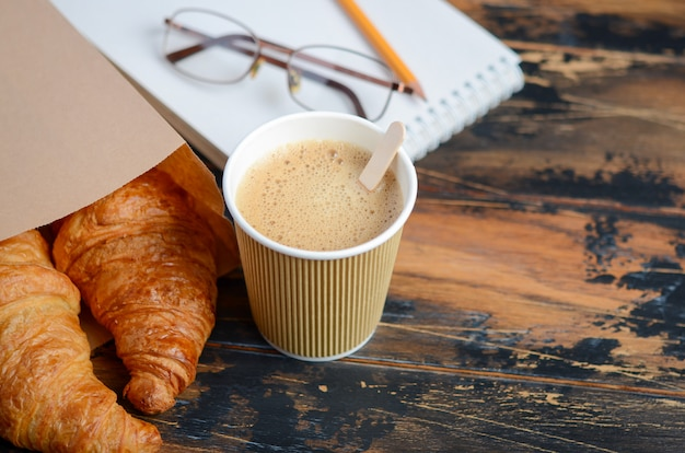 Take away coffee cup with croissant on wooden table.