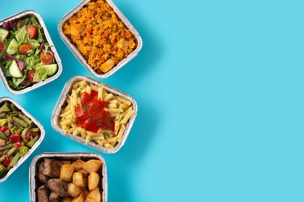 Заберите здоровую пищу в ящиках из фольги на синем
