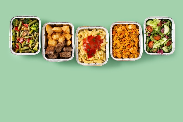 Заберите здоровую пищу в коробках из фольги на зеленом фоне