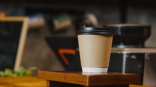 カフェレストランのバーカウンターの後ろに立っている消費者にホットコーヒーの紙コップを持ち帰ります。