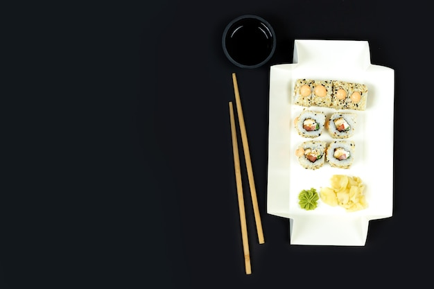 Take away japanese sushi set with chopsticks and soy sauce on dark table close-up, copy space