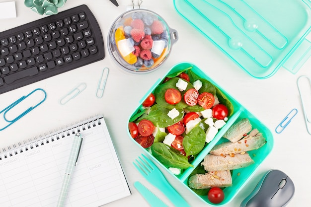Take away lunch box with fresh salad and tuna fish over the office desk with office supplies.