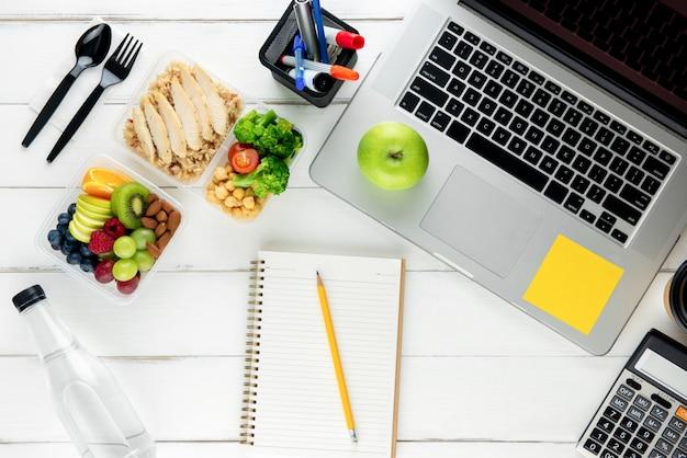 집에서 일할 준비가 된 테이블에 노트북 컴퓨터와 장비가있는 영양소가 풍부한 음식을 가져 가십시오.