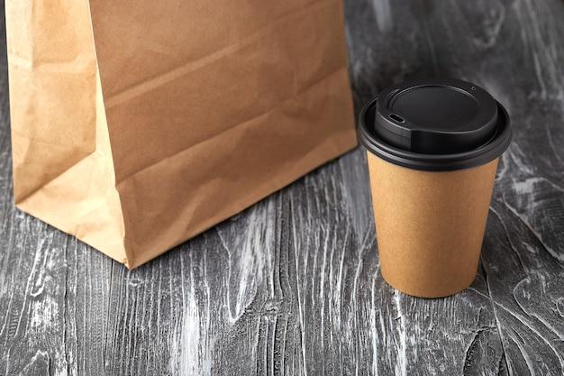 회색 나무 배경에 종이 커피 컵과 점심 가방을 빼앗아