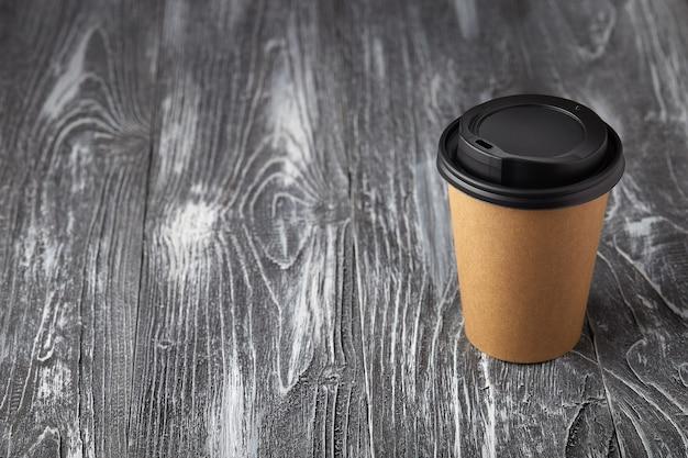 각도보기에서 회색 나무 배경에 종이 커피 컵을 빼앗아