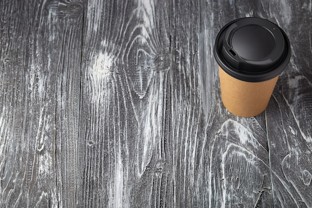 회색 나무 배경에 종이 커피 컵을 빼앗아