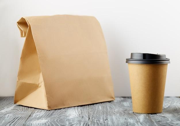 회색 나무 배경에 점심 가방과 함께 종이 커피 컵을 빼앗아