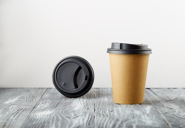 회색 나무 배경에 종이 커피 컵과 플라스틱 캡을 제거하십시오.