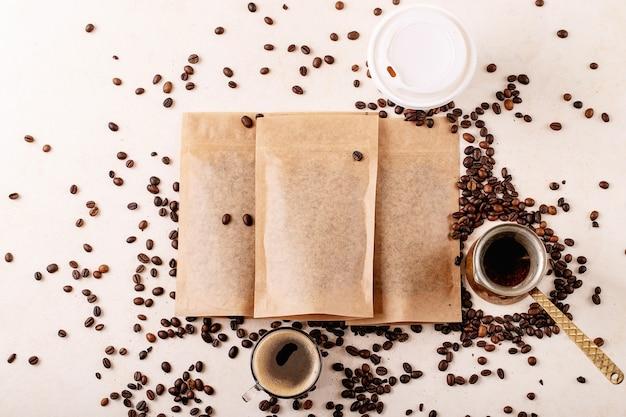 Уберите бумажный стаканчик, кофейные зерна и кофейные пакеты с пустым пространством для логотипа на белом фоне. скопируйте пространство. вид сверху