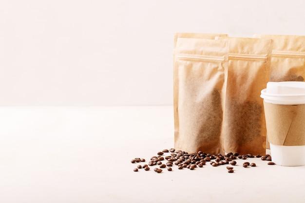 Заберите бумажный стаканчик, кофейные зерна и кофейные пакеты с пустым пространством для логотипа на белом фоне текстуры. копировать пространство