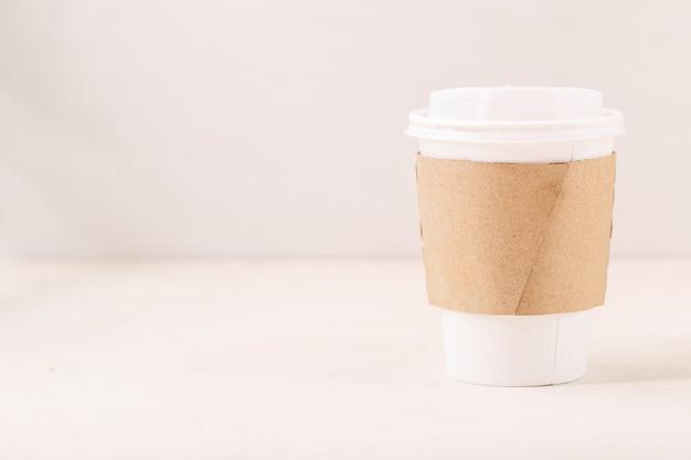 Заберите бумажный стаканчик с кофе с пространством для логотипа на чашке на белом фоне. копировать пространство