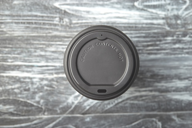 Take away plastic coffee cup cap on grey wooden background