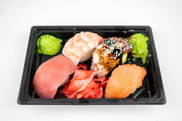 Уберите суши в пластиковой таре, розовый имбирь, васаби. концепция доставки суши