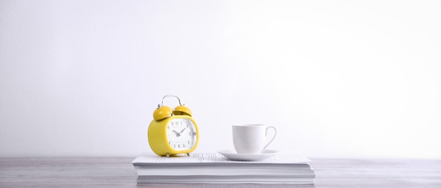 Take a break drink coffee concept. cup of coffee and clock on a stack of paper on the table