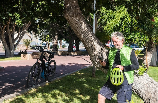 Take a break with the electric bike. front view of an elderly and sporty man 70 years leaning against a large tree trunk while checking his mobile phone. healthy lifestyle