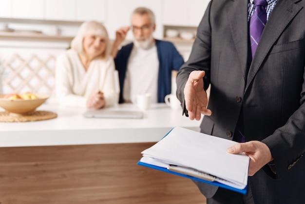 Заранее позаботьтесь о своем здоровье. уверенный, опытный, квалифицированный агент социального обеспечения, работающий и представляющий контракт рядом со старшей парой клиентов