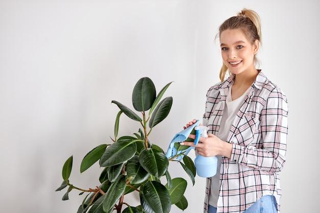 집 식물을 돌보십시오. 백인 여자는 기화기에서 녹색 식물을 물로 뿌리고 먼지를 닦아내고, 캐주얼 한 젊은 여성은 카메라를보고 웃고