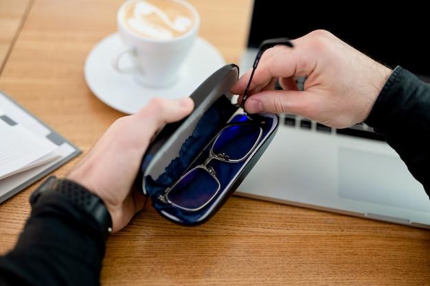 眼鏡の世話をしてください。リモートワークでのシフトの終了。若い男は万が一に備えて眼鏡を隠します。男性のフリーランサーはコーヒーショップで働いており、フラットホワイトを飲み、彼の最新のラップトップを使用しています。