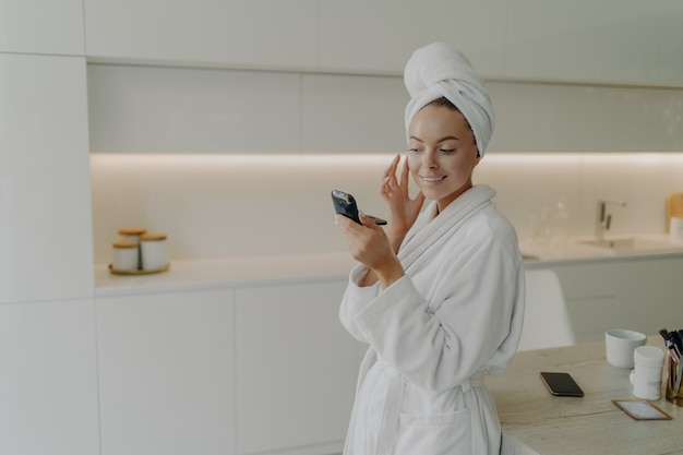 自分を大事にして下さい。バスローブを着た若い幸せな女性が、コンパクトな鏡で微笑みながら顔にスキンケア製品を塗り、現代の台所に立ち、家で化粧手順を行う