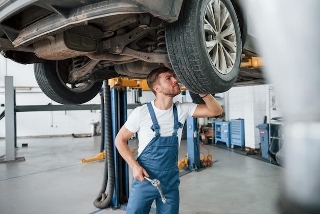 Присмотритесь. сотрудник в синей форме работает в автомобильном салоне