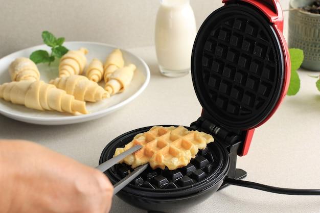 Возьмите вафли с круассанами или круассаны из магазина «электрические вафли» с помощью щипцов. домашняя выпечка на кухне, выбранный фокус. croffle - популярное в южной корее