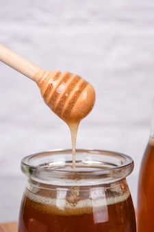 Take honey from a glass container using a wooden tool