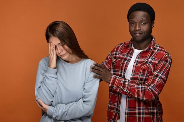 落ち着いて。ひどい頭痛のために気分が悪くなっている彼の動揺して落ち込んでいるヨーロッパのガールフレンドを抱き締めて、目を閉じて彼女の頭に触れる魅力的なスタイリッシュなアフリカ系アメリカ人の男