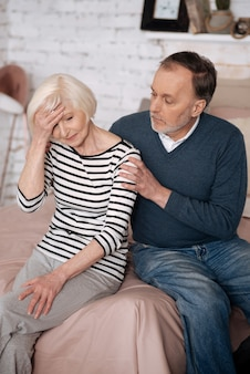 落ち着いて。手で彼女の額に触れている彼の欲求不満の妻をサポートする年配の男性のクローズアップ。
