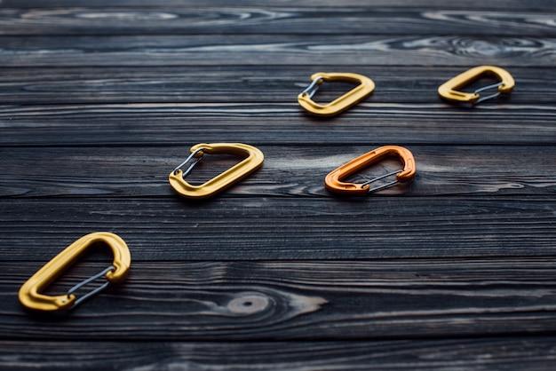 あなたのためにそれを極端な週末の活動にしてください。隔離された登山用具。木製のテーブルの上に横たわっているカラビナの部品。