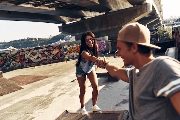 내 손을 잡아! 야외 스케이트 공원에서 시간을 보내는 동안 친구에게 올라가려고 하는 아름다운 젊은 여성