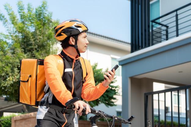 Азиатский курьер человека проверяя адрес клиента в карте в телефоне на велосипеде поставляя еду на улицах городка с горячей доставкой еды от take out и ресторанов к дому.