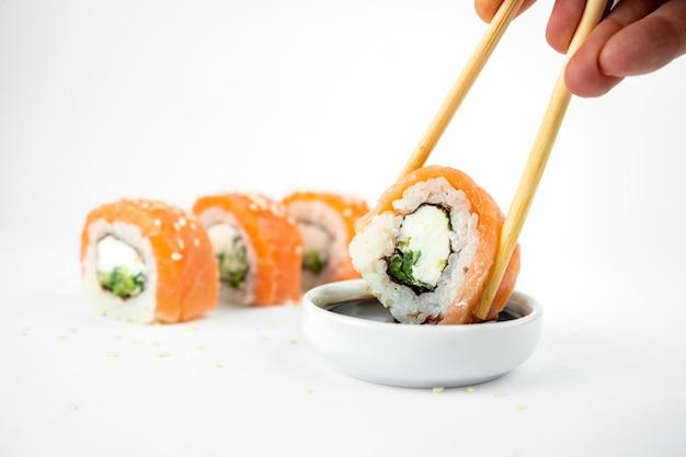 Возьмите роллы филадельфия маки с бамбуковой палочкой для еды на белом фоне