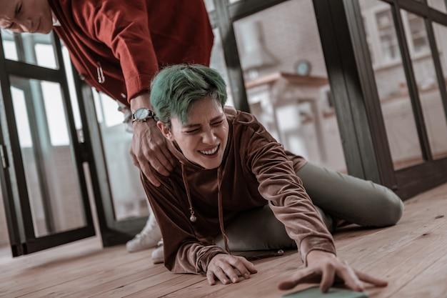 電話を取る。家庭内暴力を報告するために電話を取り、警察に通報しようとする緑髪の泣いている女性